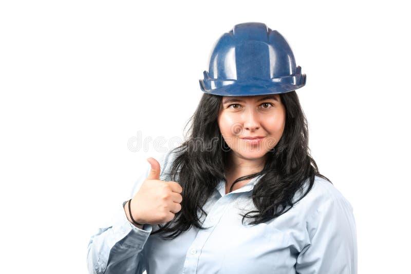 Jonge aantrekkelijke glimlachende donkerbruine vrouweningenieur of architect met blauwe veiligheidshoed die duimen tonen die omho royalty-vrije stock foto
