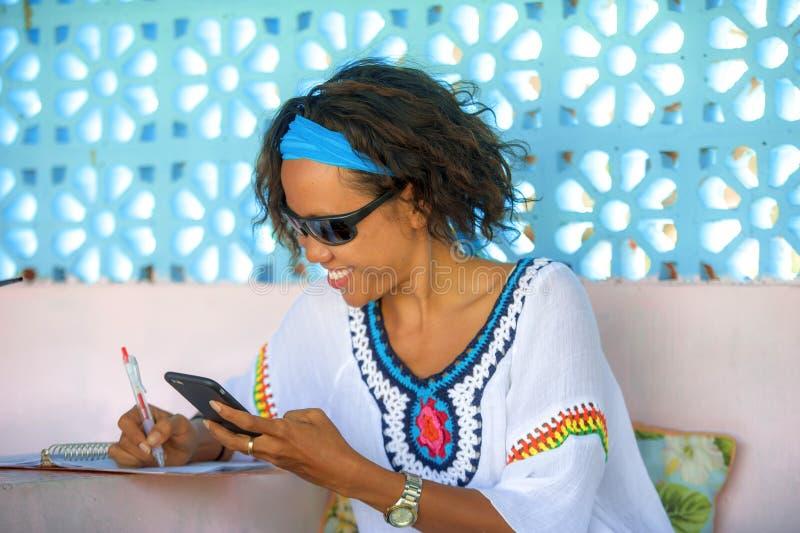 Jonge aantrekkelijke hipster en het exotische kijken gelukkig en ontspannen meisje gebruikend de sociale media die van Internet a stock afbeeldingen