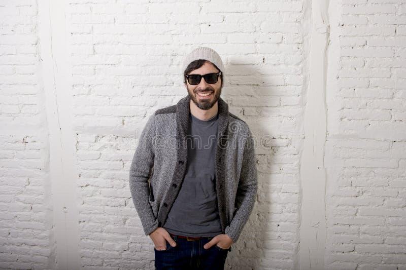 Jonge aantrekkelijke hipster en in stijl die mens stellen koel met zich houding informeel kleden kijken stock afbeeldingen