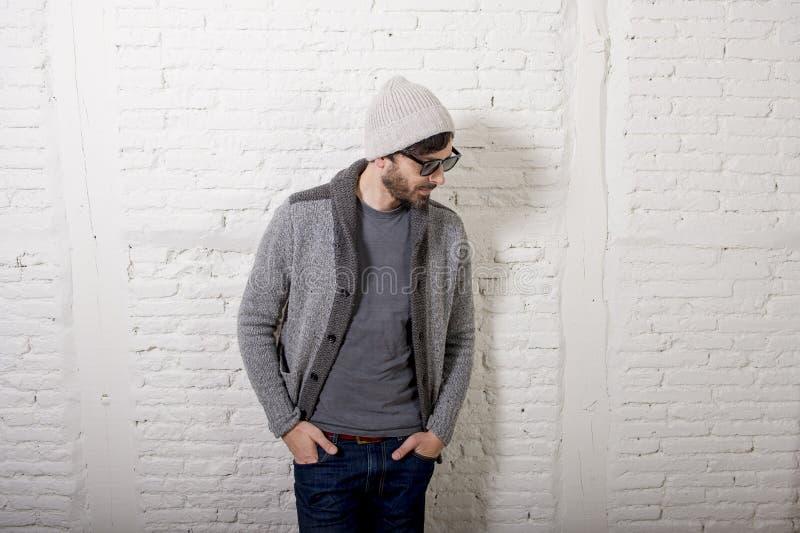 Jonge aantrekkelijke hipster en in stijl die mens stellen koel met zich houding informeel kleden kijken stock foto