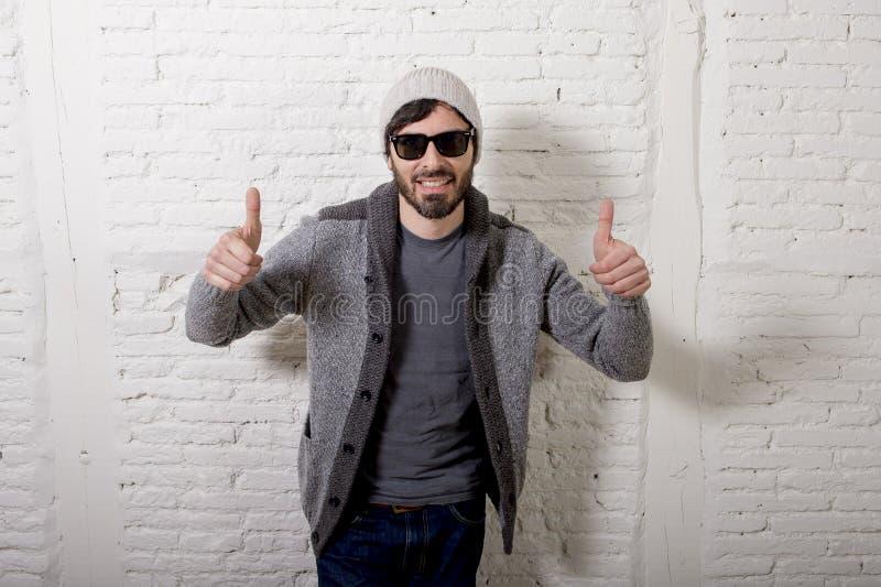 Jonge aantrekkelijke hipster en in stijl die mens stellen koel met zich houding informeel kleden kijken stock fotografie