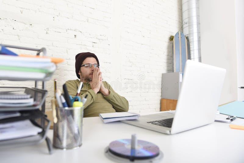 Jonge aantrekkelijke hipsterzakenman die met computer in modern huisbureau werken royalty-vrije stock foto's