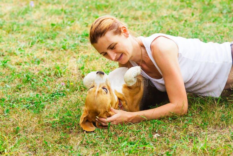 Jonge aantrekkelijke hondeigenaar die op gras met haar huisdier leggen stock foto's