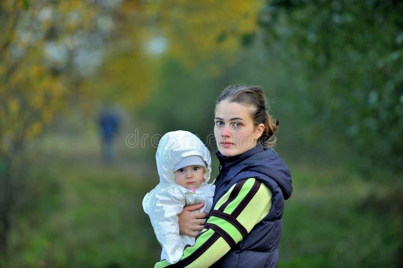 Jonge Aantrekkelijke jonge moeder die een klein meisje in haar wapens houden bij zonsonderganglicht Gang in de de herfst warme av stock afbeelding