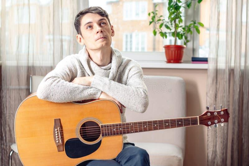 Jonge aantrekkelijke mannelijke musicuszitting op een stoel die een akoestische gitaar houden Concept muziek als hobby stock afbeelding