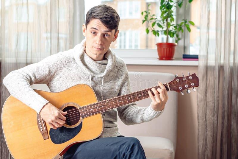 Jonge aantrekkelijke mannelijke musicuszitting op een stoel die akoestische gitaar in ruimte spelen Concept muziek als hobby stock afbeelding
