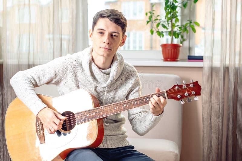 Jonge aantrekkelijke mannelijke musicuszitting op een stoel die akoestische gitaar spelen Concept muziek als hobby stock fotografie