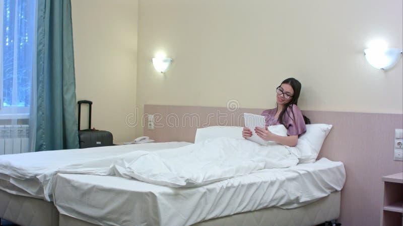 Jonge aantrekkelijke meisjesvrouw in een hotelruimte die op het bed liggen die een tabletcomputer met behulp van die videopraatje royalty-vrije stock afbeeldingen