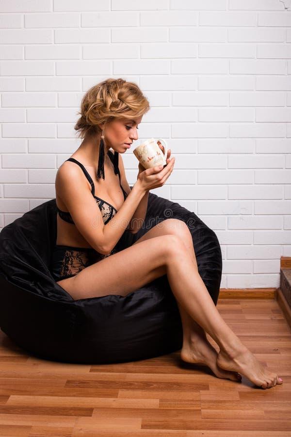 Jonge aantrekkelijke meisjeszitting op een stoel met een GLB van thee stock afbeelding