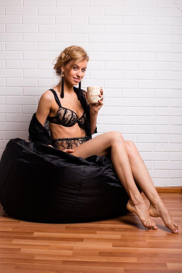 Jonge aantrekkelijke meisjeszitting op een stoel met een GLB van thee royalty-vrije stock afbeeldingen
