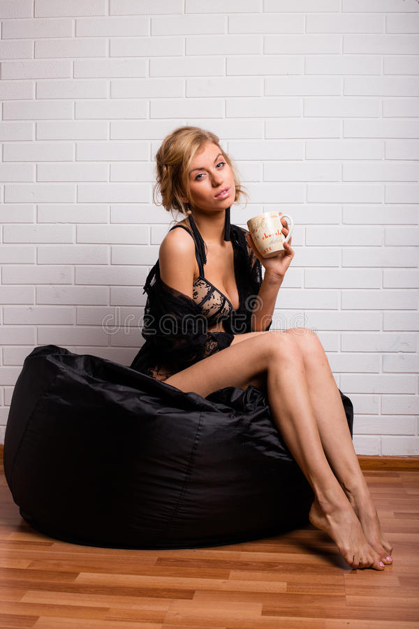 Jonge aantrekkelijke meisjeszitting op een stoel met een GLB van thee royalty-vrije stock foto