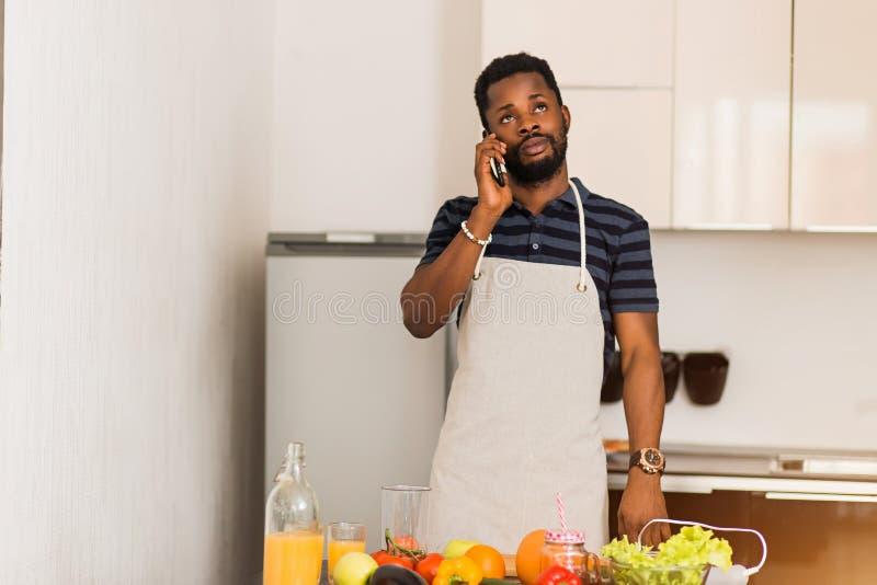Jonge aantrekkelijke mens die op de telefoon in de keuken spreken stock fotografie