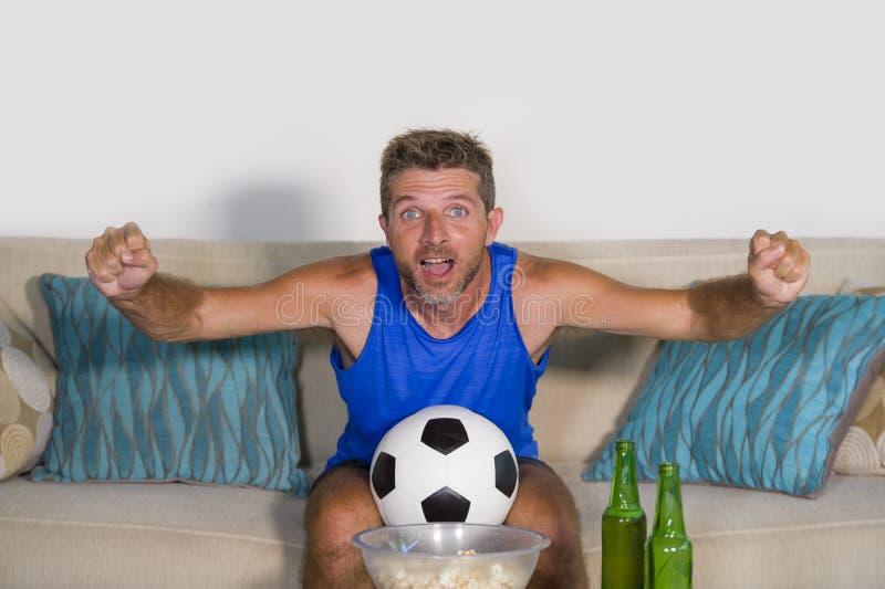 Jonge aantrekkelijke mens gelukkige en opgewekte het letten op voetbalwedstrijd op TV-het vieren overwinningsdoel gek en spastisc royalty-vrije stock afbeeldingen