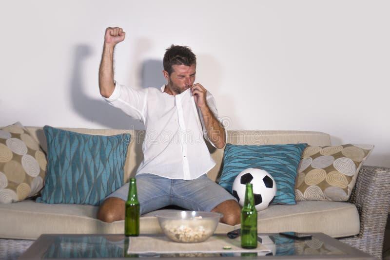 Jonge aantrekkelijke mens gelukkige en opgewekte het letten op voetbalwedstrijd op van het de overwinningsdoel van TV het vierend royalty-vrije stock fotografie