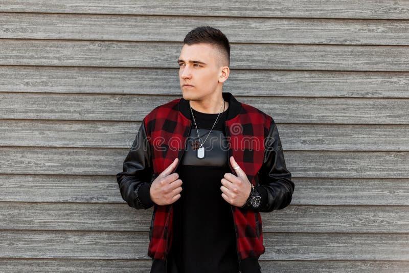 Jonge aantrekkelijke mens in in zwart en rood geruit jasje in een in zwarte t-shirt met amulet het stellen stock foto's