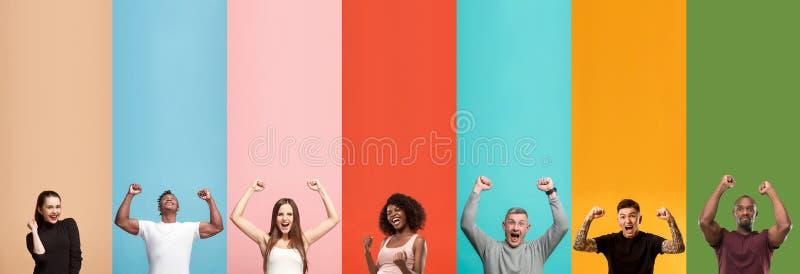 Jonge aantrekkelijke mensen kijken die die op multicolored achtergrond worden verbaasd stock fotografie