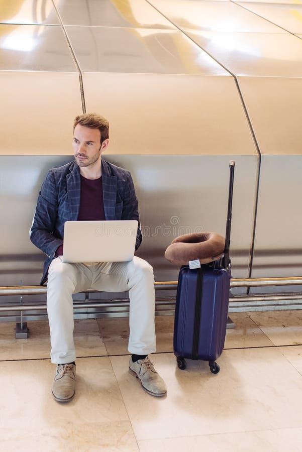Jonge aantrekkelijke mensenzitting bij de luchthaven die met een lapto werken stock foto's