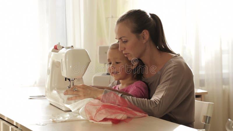 Jonge aantrekkelijke moeder die aan naaimachine met haar weinig leuke dochter werken stock videobeelden