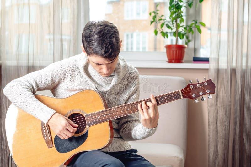 Jonge aantrekkelijke musicuszitting op een stoel die akoestische gitaar spelen Concept muziek als hobby stock foto