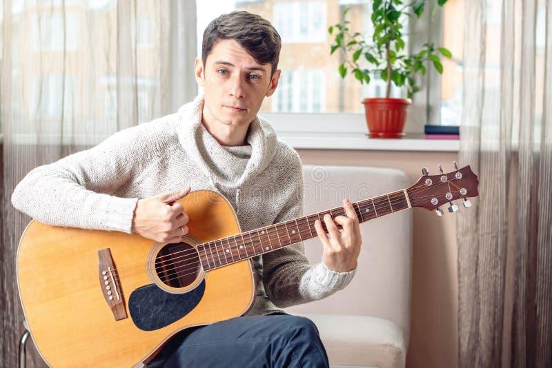 Jonge aantrekkelijke musicuszitting op een stoel die akoestische gitaar spelen Concept muziek als hobby royalty-vrije stock afbeelding