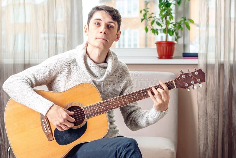 Jonge aantrekkelijke musicuszitting op een stoel die akoestische gitaar spelen Concept muziek als hobby stock afbeelding