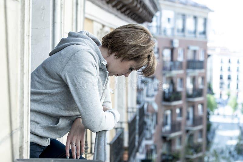 Jonge aantrekkelijke ongelukkige zelfmoordvrouw die aan depressie lijden die neer op het balkon thuis kijken stock fotografie