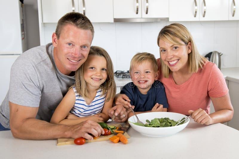 Jonge aantrekkelijke paarmoeder en vader die salade samen met weinig zoon en jonge mooie dochter in gezonde vegetab voorbereiden royalty-vrije stock afbeelding
