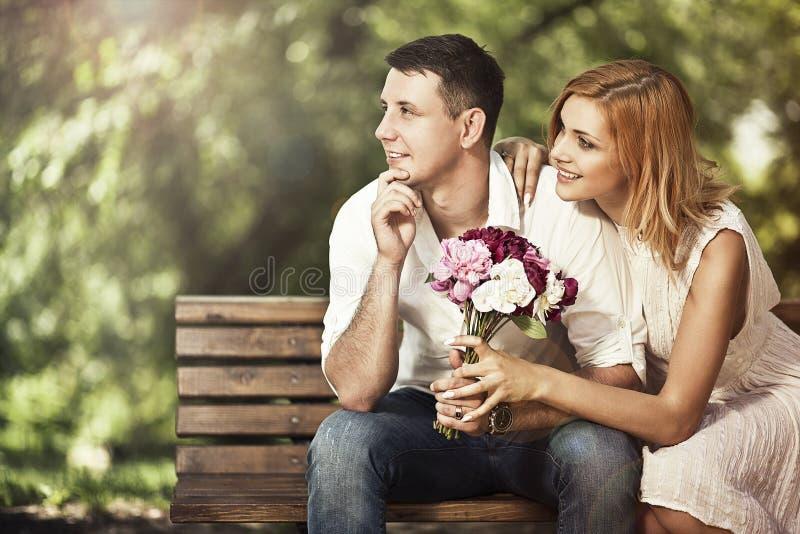Jonge aantrekkelijke paarzitting op bank in het park en embraci royalty-vrije stock afbeelding
