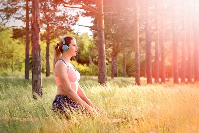 Jonge aantrekkelijke slanke vrouw die oortelefoons dragen, die yoga doen, die in het park mediteren Gezond levensstijlconcept stock afbeelding