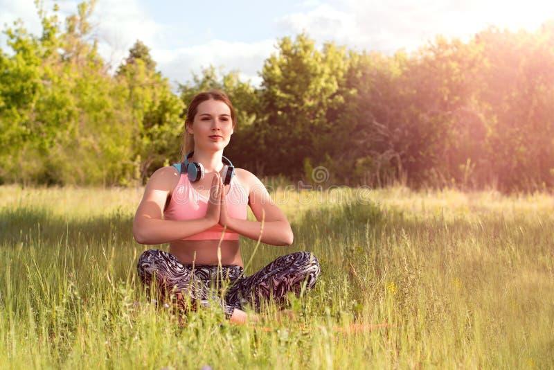 Jonge aantrekkelijke slanke vrouw die oortelefoons dragen, die yoga doen, die in het park mediteren Gezond levensstijlconcept stock foto