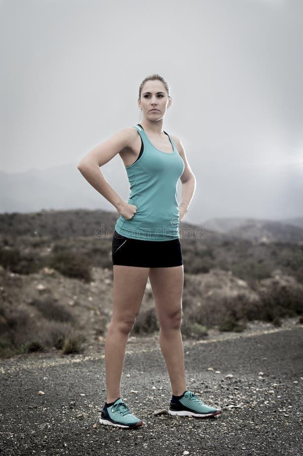 Jonge aantrekkelijke sportvrouw in het runnen van hemd en borrels stellen uitdagend en koel in asfaltweg voor berg royalty-vrije stock foto's
