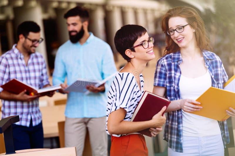 Jonge aantrekkelijke studenten die tijd in bibliotheek doorbrengen stock foto