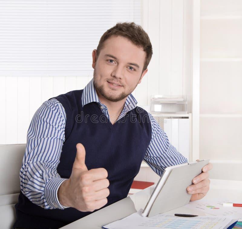 Jonge aantrekkelijke succesvolle manager met duim omhoog op kantoor. stock fotografie