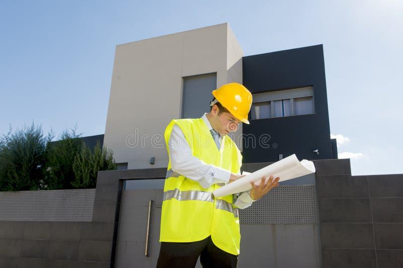 Jonge aantrekkelijke voormanarbeider die de bouwblauwdrukken controleren die in openlucht bouwhelm dragen stock afbeeldingen