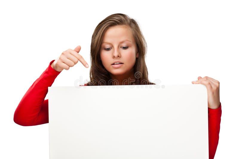 Jonge aantrekkelijke vrouw achter lege raad op witte achtergrond royalty-vrije stock foto's