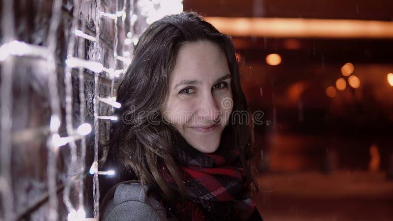 Jonge aantrekkelijke vrouw in de dalende sneeuw bij Kerstnacht die de camera bekijken die zich dichtbij lichtenmuur bevinden, royalty-vrije stock afbeeldingen