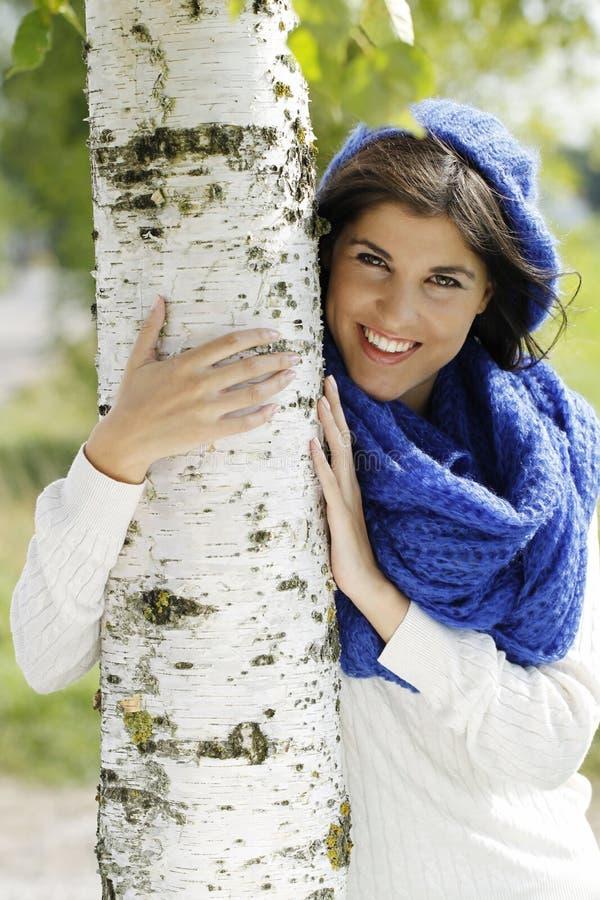 Jonge aantrekkelijke vrouw dicht bij een berkboom stock foto