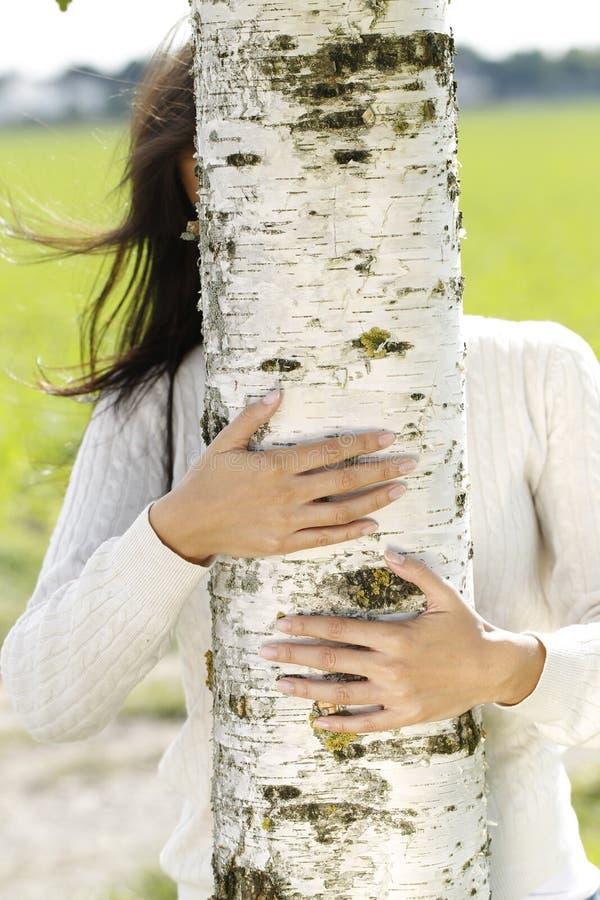 Jonge aantrekkelijke vrouw dicht bij een berkboom stock afbeeldingen