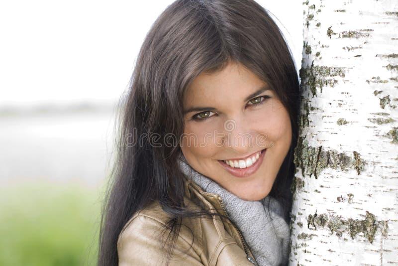 Jonge aantrekkelijke vrouw dicht bij een berkboom stock afbeelding