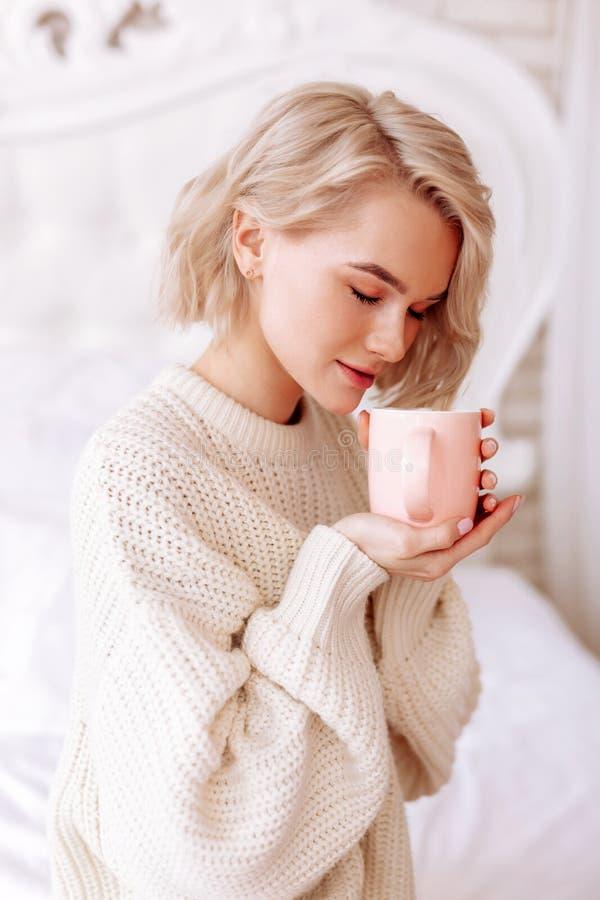 Jonge aantrekkelijke vrouw die blije ruikende ochtendkoffie voelen stock afbeeldingen