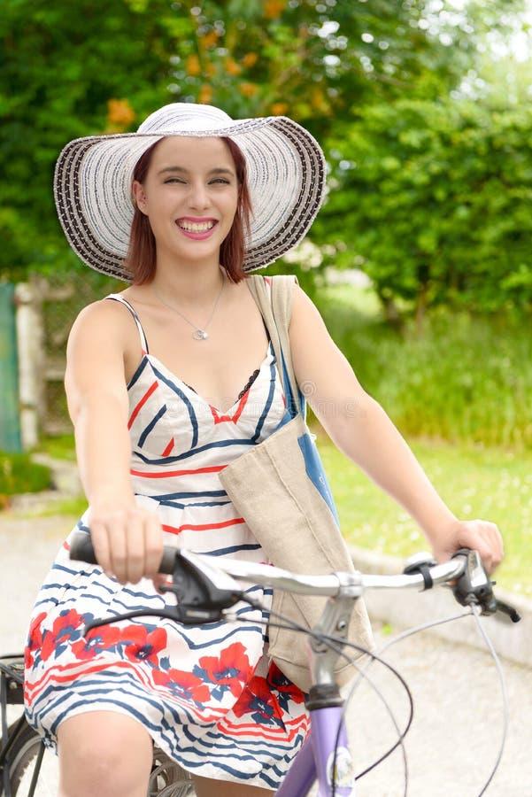 Jonge aantrekkelijke vrouw die een fiets berijdt stock foto's