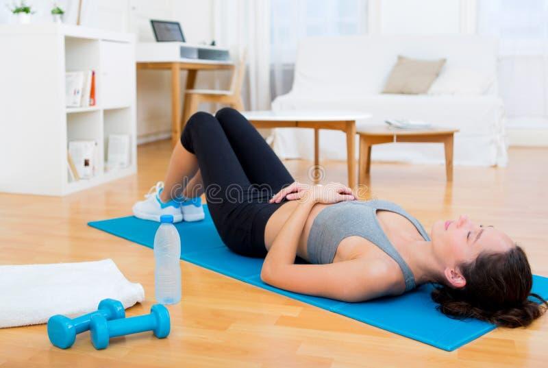 Jonge aantrekkelijke vrouw die een rust na sport hebben stock afbeelding