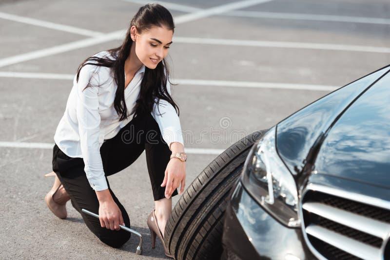 Jonge aantrekkelijke vrouw die in formele slijtage dichtbij autoband hurken met handvatmoersleutel stock afbeeldingen