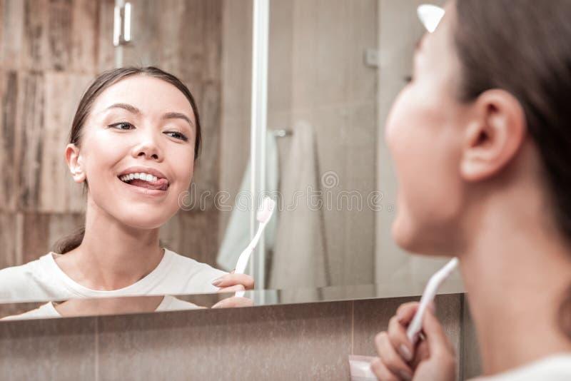 Jonge aantrekkelijke vrouw die haar aardige witte tanden bekijken royalty-vrije stock afbeelding