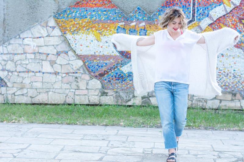 Jonge aantrekkelijke vrouw die met rode lippen in witte vrijetijdskleding het stellen in de straat lopen royalty-vrije stock afbeelding
