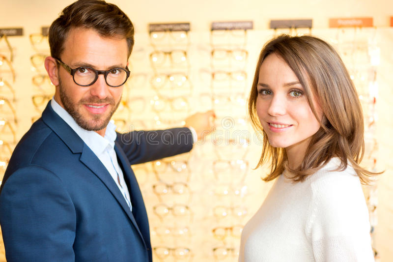 Jonge aantrekkelijke vrouw die nieuwe glazen met opticien testen royalty-vrije stock foto's