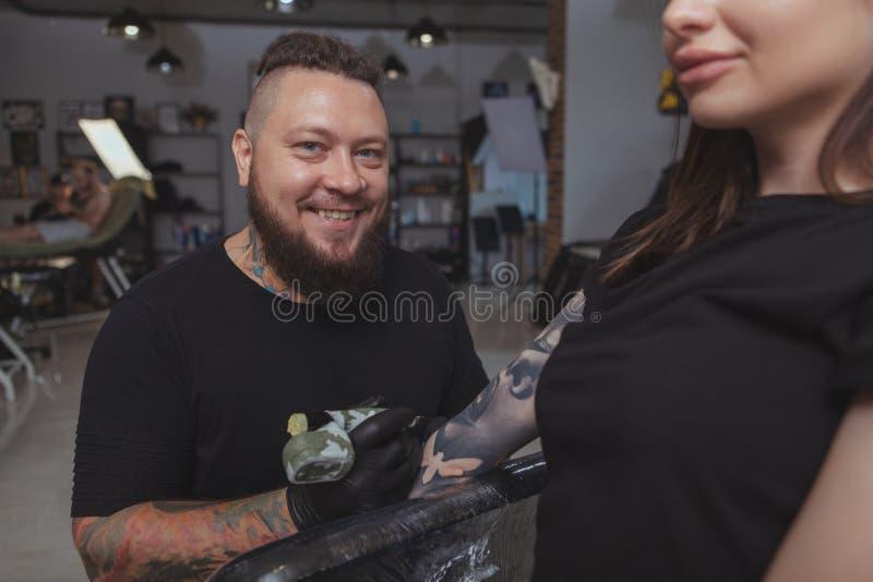 Jonge aantrekkelijke vrouw die nieuwe tatoegering krijgen door professionele tattooist royalty-vrije stock afbeelding