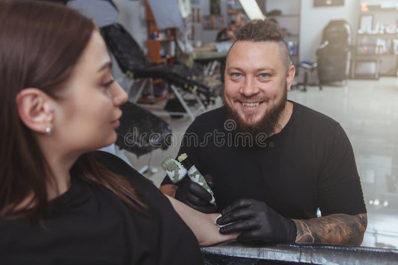 Jonge aantrekkelijke vrouw die nieuwe tatoegering krijgen door professionele tattooist stock foto