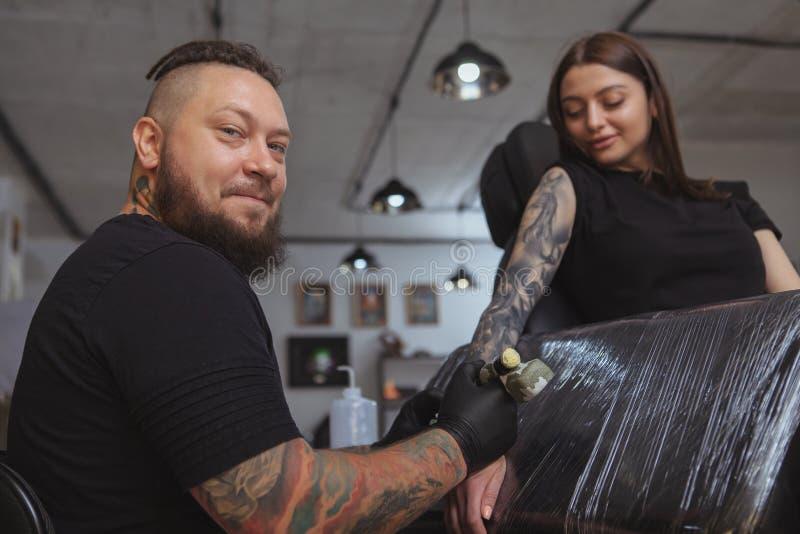 Jonge aantrekkelijke vrouw die nieuwe tatoegering krijgt door professionele tattooist royalty-vrije stock fotografie