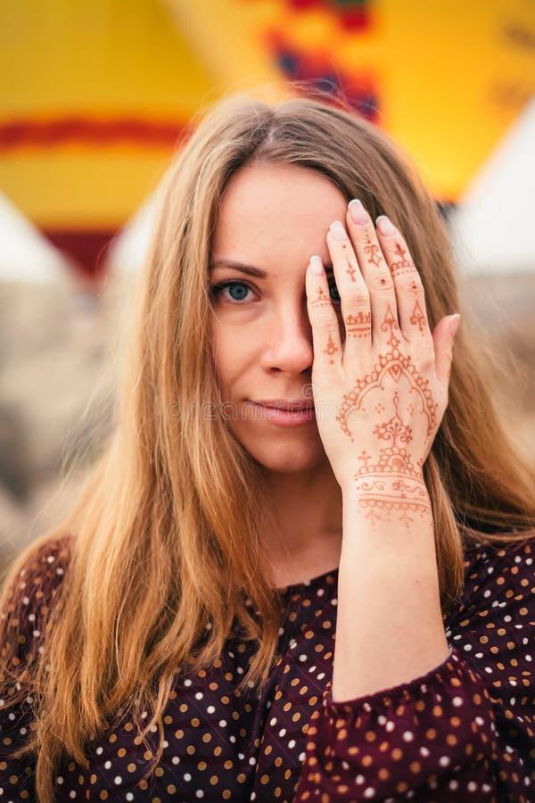Jonge aantrekkelijke vrouw die oog behandelen met mehendihand stock afbeelding